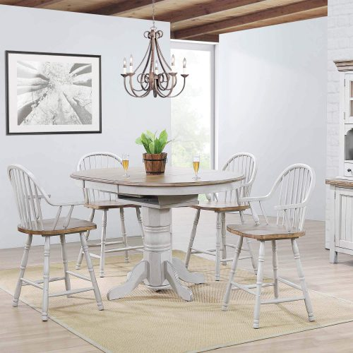 Country Grove Collection - Round pedestal pub table in distressed gray with Oak top and four Windsor bar height stools with arms in dining room setting DLU-CG4260CB30AGO5